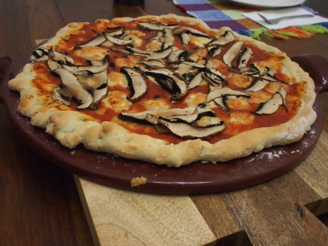 Baked pizza with cheese and mushrooms topping sitting on a baking stone and a wooden cutting board