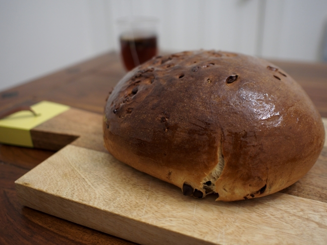 Loaf of bread resting on a cutting board. The chocolate chips are visible in the bread. In the background there is a glass filled with tea.