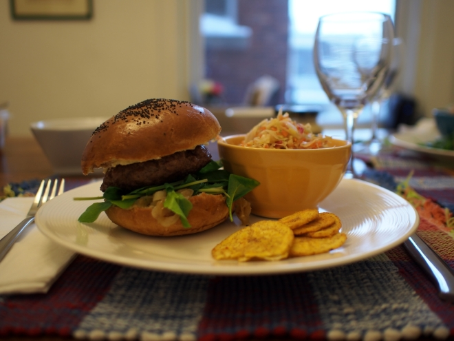 A plate with a burger. We can see the buns covered in poppy seeds and rocket leaves inside. On the side of the dish, as small bowl filled with coleslaw and in front of it some plantain chips.