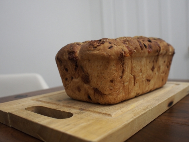 A loaf of bread is resting on a cutting board