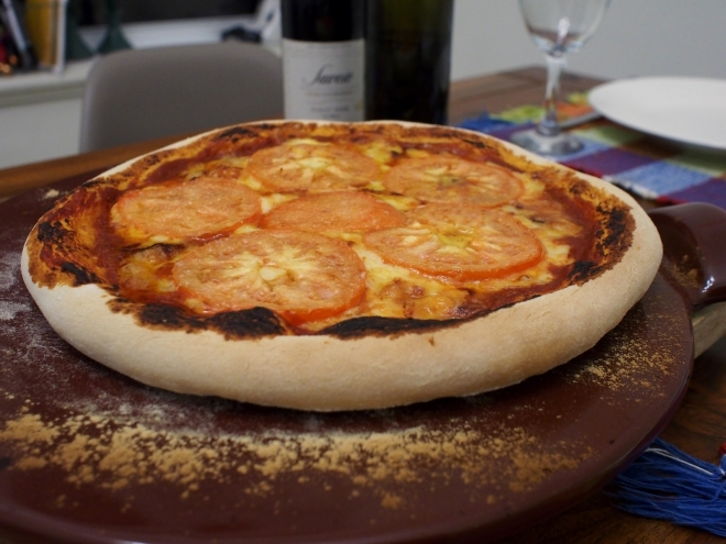 A cheese and tomato pizza is resting on a pizza stone. On the background there is a bottle of wine, a bottle of olive oil, a plate and a wine glass