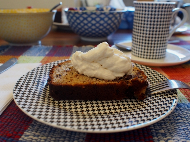 A slice of bananabread is cut on a plate. There is an amount of whipped cream on top of the slice. In the background there is a cup of coffee and a couple of bowls.